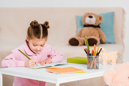 adorable focused child writing with pencil and studying at home Stock fotó