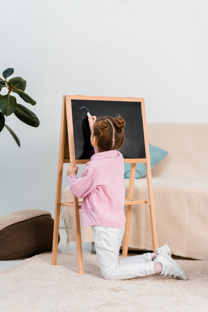 back view of cute kid kneeling on carpet and writing on chalkboard