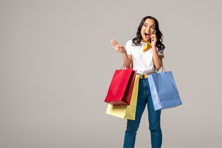 Excited young asian woman holding colorful shopping bags and emotionally talking on smartphone isolated on grey Stock Photo