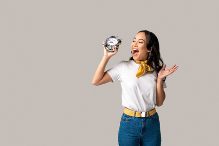 Smiling asian woman holding alarm clock in raised hand isolated on grey Stok Fotoğraf