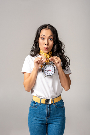 Surprised young asian woman holding alarm clock in front of herself isolated in grey