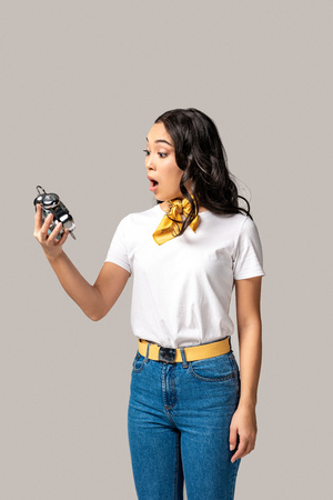 Surprised young asian woman in white t-shirt and blue jeans holding alarm clock isolated in grey Stok Fotoğraf