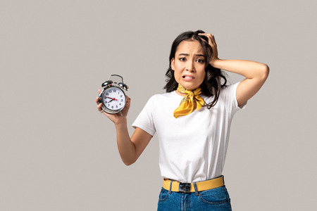 Shocked young asian woman showing alarm clock and holding hand on head isolated in grey Stok Fotoğraf