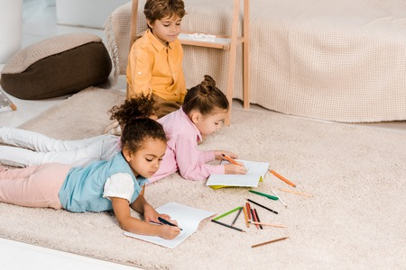 high angle view of beautiful multiethnic kids lying on carpet and studying together