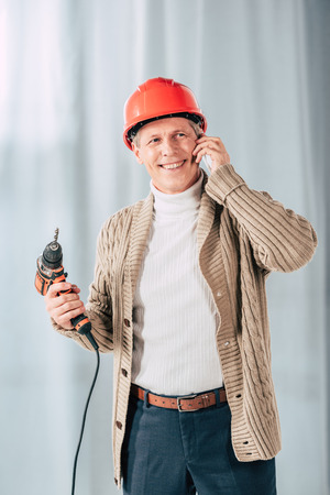 middle aged man in beige cardigan holding screwdriver and talking on smartphone at home