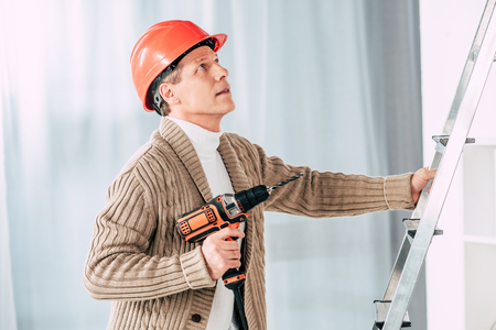 man in beige cardigan climbing with screwdriver on ladder at home Stock Photo