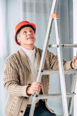 middle aged man in beige cardigan climbing on ladder at home