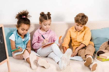 adorable multiethnic children sitting on sofa and studying together