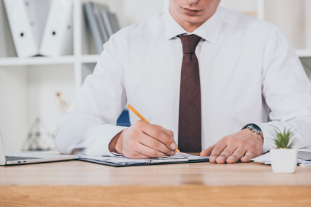 cropped view of businessman filling in compensation claim at workspace Фото со стока