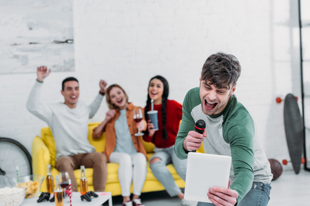 cheerful young men singing karaoke while multiethnic friends enjoying drinks and snacks Stockfoto