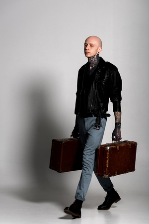 handsome tattooed man in leather jacket holding suitcases and walking on grey Stockfoto