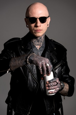 bald tattooed man in leather jacket and sunglasses opening soda can isolated on grey
