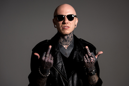 aggressive tattooed man in leather jacket and sunglasses showing middle fingers isolated on grey Reklamní fotografie