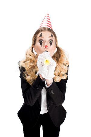 female clown in suit blowing in birthday blower isolated on white Stock Photo