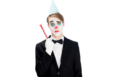 clown in suit and birthday cap holding blower isolated on white