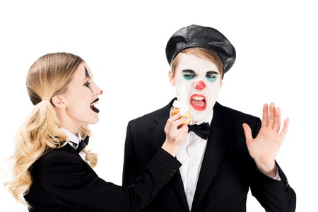 cheerful female clown throwing cupcake in face of dissatisfied man isolated on white Stock Photo