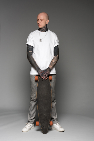 full length view of handsome bald tattooed man in white t-shirt standing with skateboard and looking away on grey