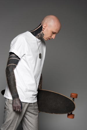 side view of bald tattooed man in white t-shirt holding skateboard and looking down isolated on grey 版權商用圖片