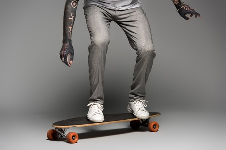 low section of stylish tattooed man balancing on skateboard on grey