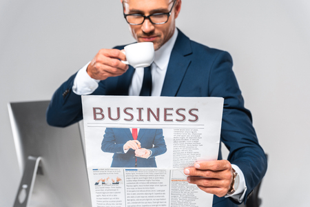 handsome businessman drinking coffee and reading business newspaper isolated on white