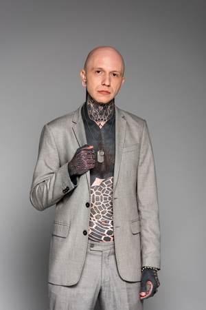 handsome bald man with tattoos on chest wearing suit and looking at camera isolated on grey 스톡 콘텐츠