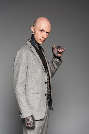side view of handsome bald tattooed man in suit holding dog tag on chain and looking at camera isolated on grey Stock Photo