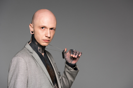 handsome bald tattooed man in suit holding dog tag on chain and looking at camera isolated on grey