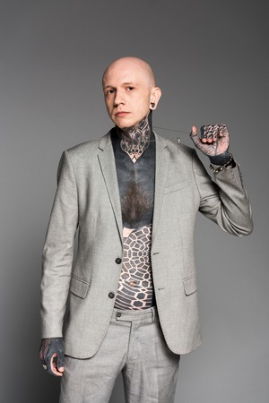 stylish tattooed man in grey suit holding chain and looking at camera isolated on grey