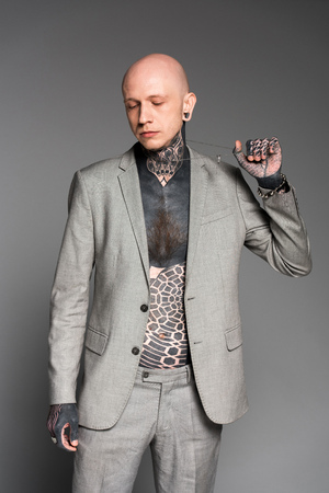 stylish tattooed man in grey suit holding chain and looking down isolated on grey 版權商用圖片