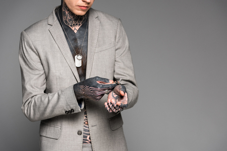 cropped shot of stylish tattooed man adjusting bracelet isolated on grey