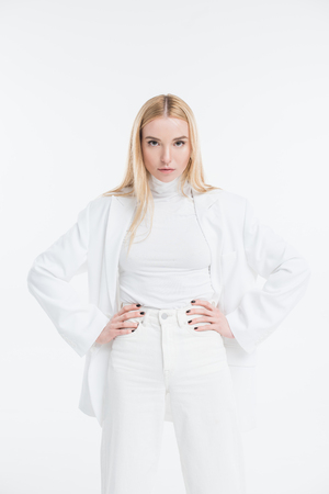 attractive caucasian blonde woman in fashionable white clothes posing with hands akimbo isolated on white