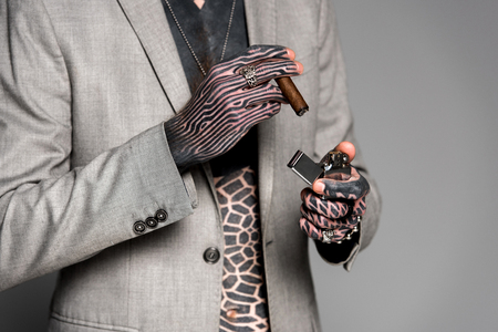 mid section of tattooed man in suit jacket holding cigar and lighter isolated on grey Banque d'images