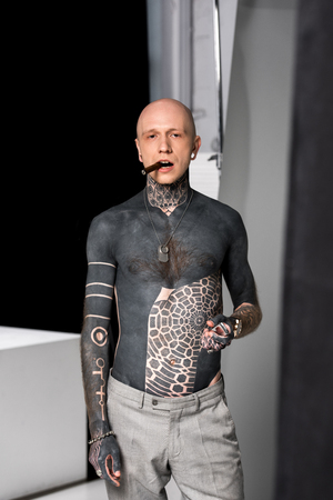 bald tattooed bare-chested man smoking cigar and looking at camera in studio