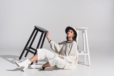 attractive african american girl in stylish white clothes and hat sitting near black and white chairs on white Imagens
