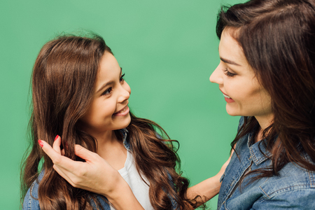 portrait of mother and daughter smiling and looking at each other isolated on green Фото со стока