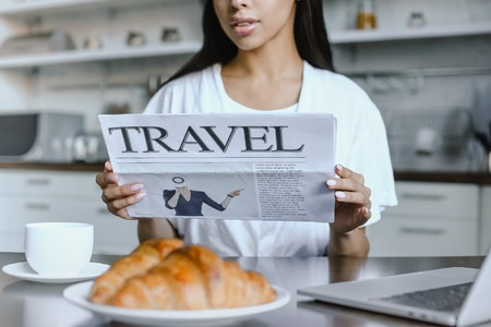 cropped image of mixed race girl in white robe reading travel newspaper in morning in kitchen