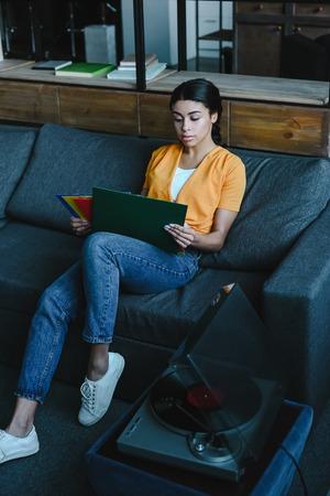 beautiful mixed race girl in orange shirt choosing vinyl on sofa in living room