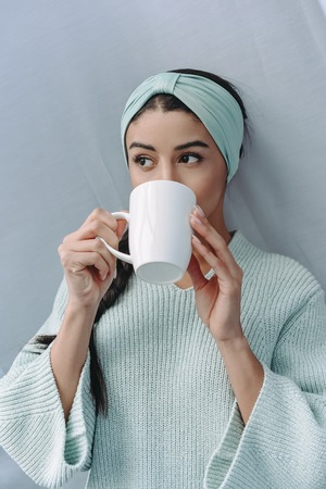 attractive mixed race girl in turquoise sweater and headband drinking tea at home