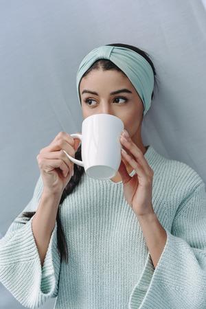 attraktives Mischlingsmädchen in türkisfarbenem Pullover und Stirnband, das zu Hause Tee trinkt
