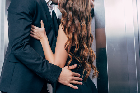 cropped view of couple passionately kissing near elevator