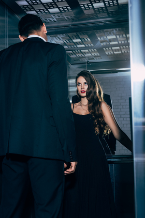 beautiful woman in black dress passionately looking at man in elevator Фото со стока