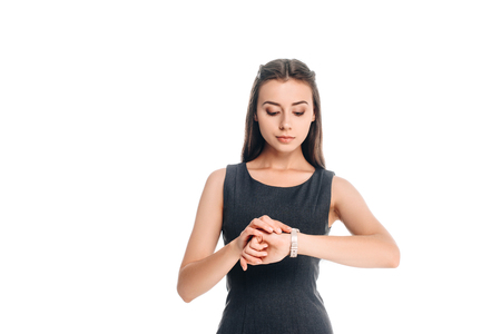 portrait of woman in stylish black dress checking time isolated on white