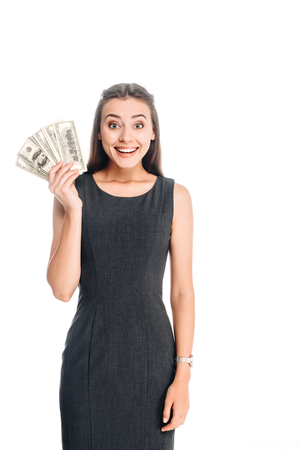 cheerful young woman in black dress holding dollar banknotes isolated on white Stock Photo