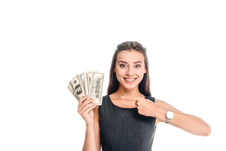 smiling woman in black dress pointing at dollar banknotes isolated on white Imagens