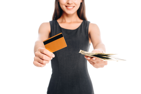 cropped shot of smiling woman in black dress with credit card and cash isolated on white