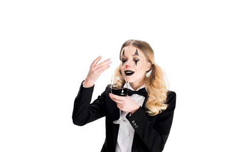 female clown in suit smelling wine while holding glass isolated on white
