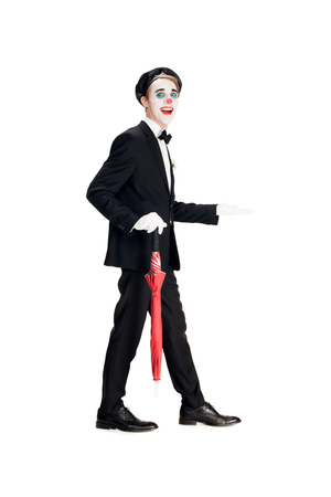 cheerful clown in suit and black beret holding umbrella while walking isolated on white Banco de Imagens