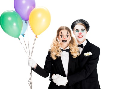 happy clowns hugging and holding helium balloons isolated on white Stock Photo
