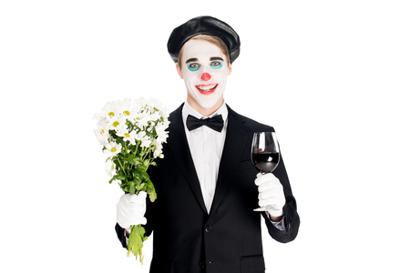 smiling clown holding flowers and glass on wine in hands isolated on white 免版税图像