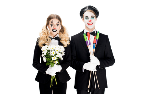 cheerful couple of clowns holding flowers and firecrackers in hands isolated on white